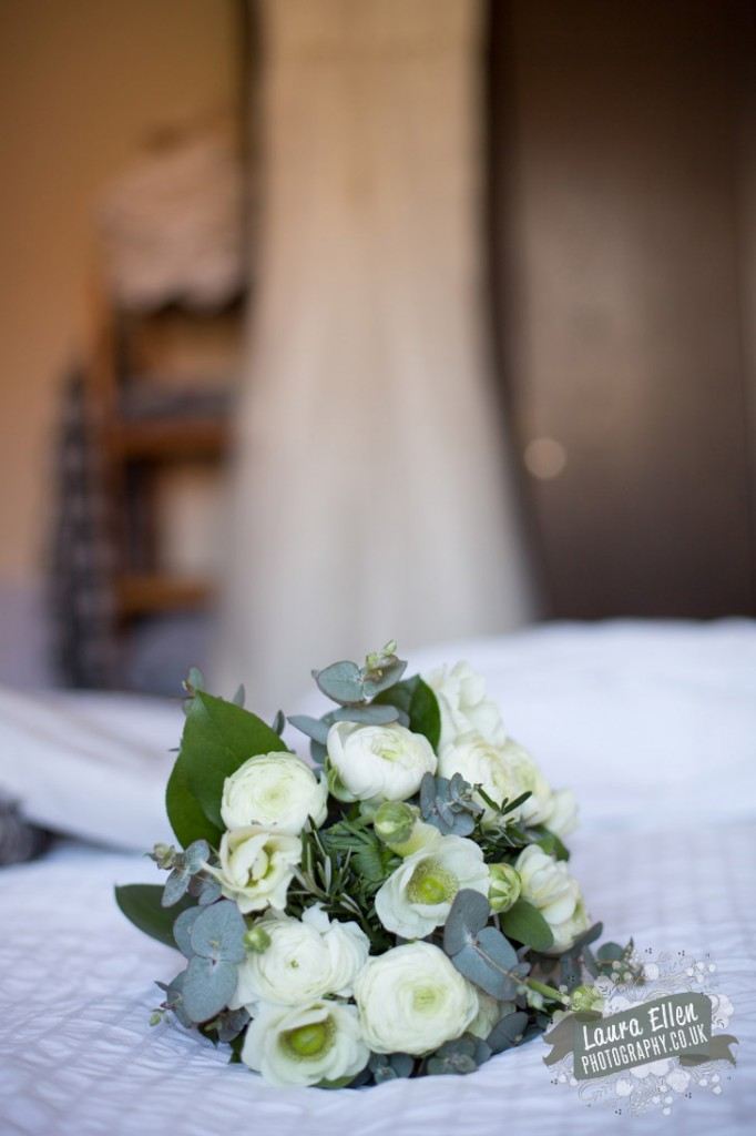 White and cream wedding bouquet of white anemone white ranunculus eucalyptus and rosemary