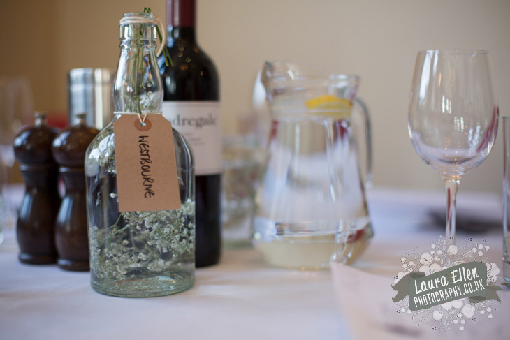 Flip top bottles and gypsophila wedding table centrepieces