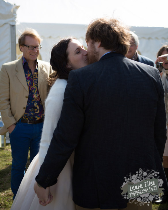 Bride kisses her Groom at marquee wedding