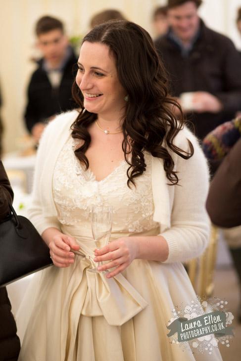 Bride wearing ivory lace and blush pink wedding dress