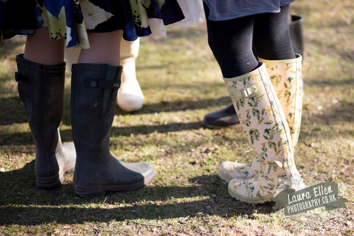 Wedding guests wearing wellington boots at countryside wedding