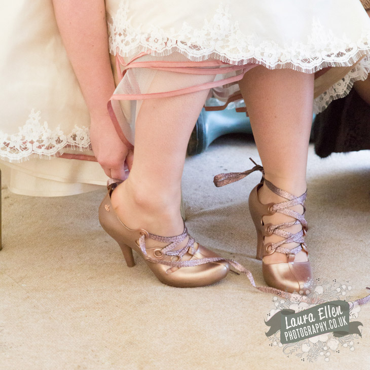 Brides putting on her rose gold Vivienne Westwood shoes