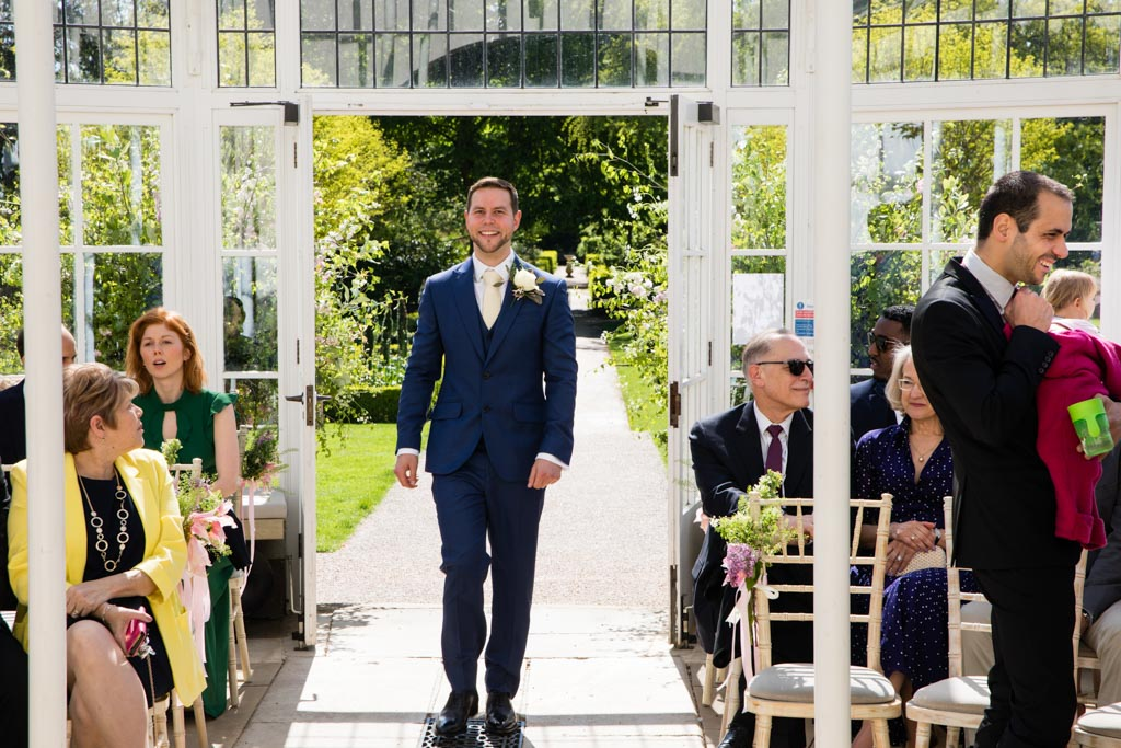 groom walking into Chiswick House and Gardens conservatory