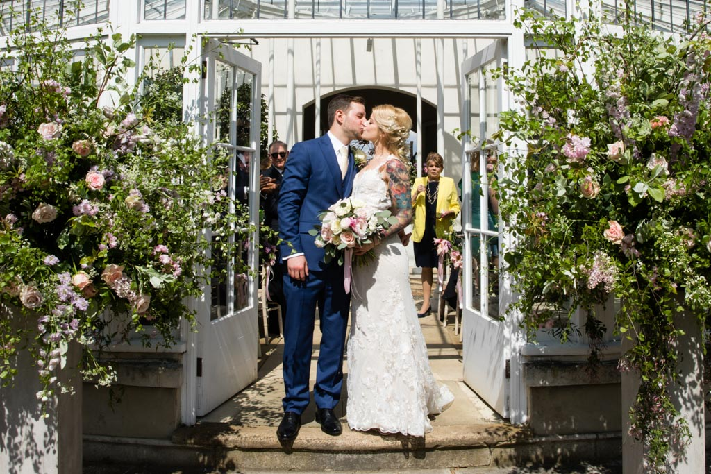 bride and groom kiss at Chiswick House and Gardens Conservatory