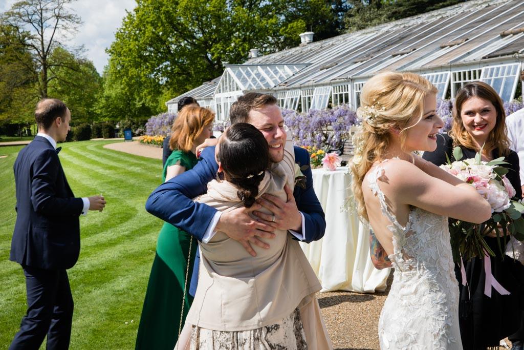 guests hug groom in gardens