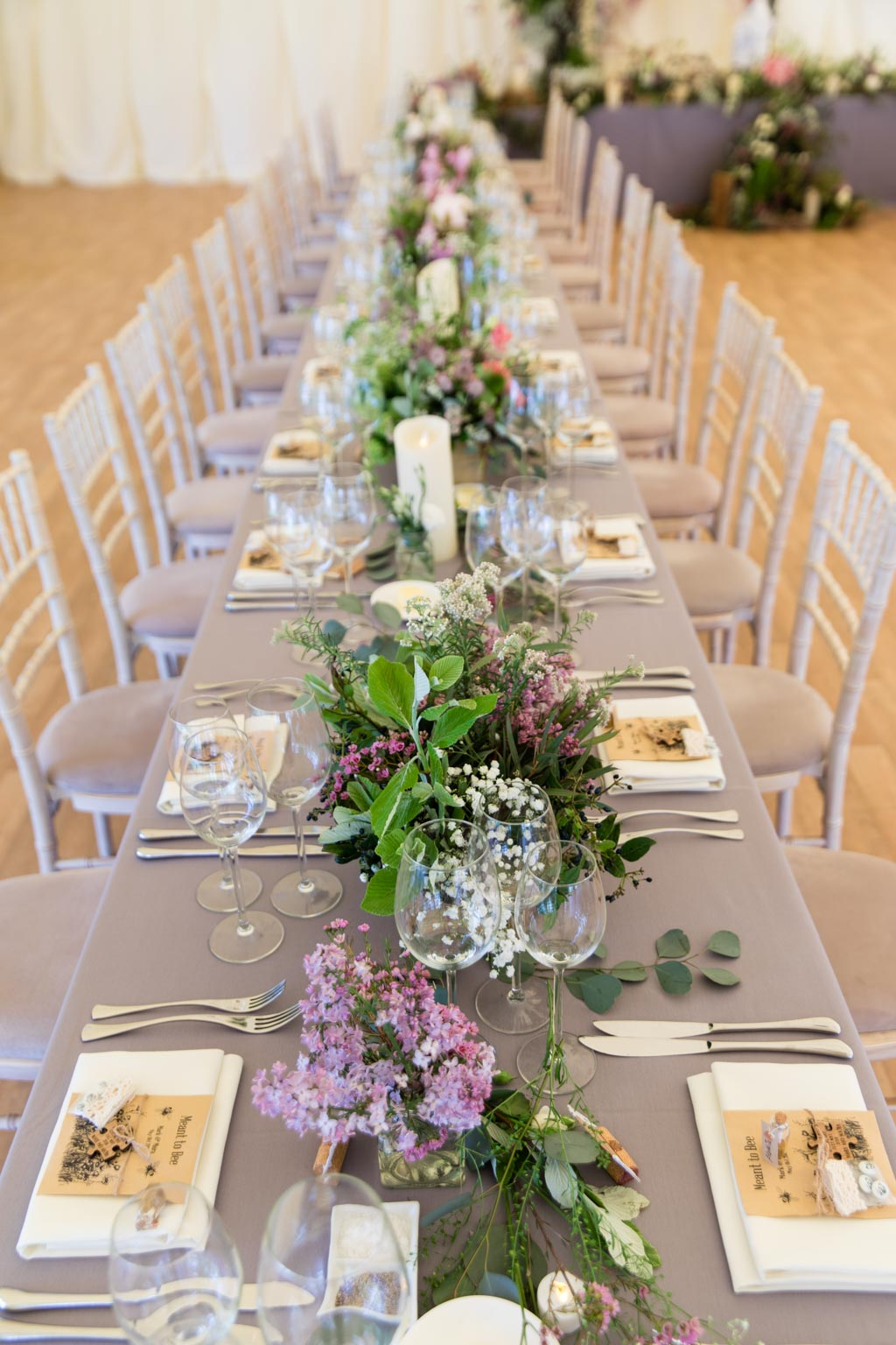 banquet style wedding tables with grey table cloths and floral arrangements