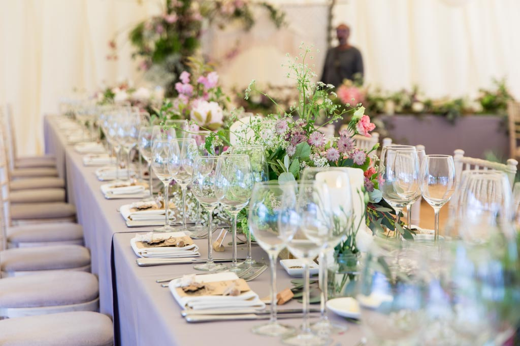 wedding reception tables with low rise flowers and glasses