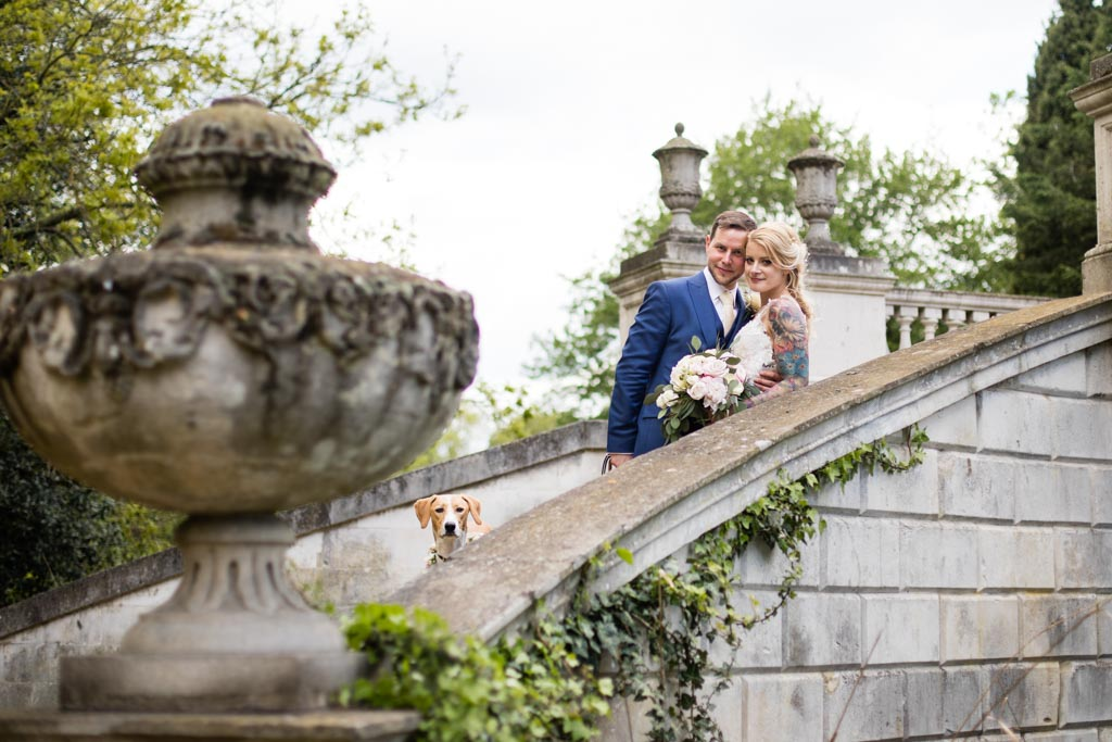 bride and groom on the bridge at Chiswick House and Gardens with dog peeking out