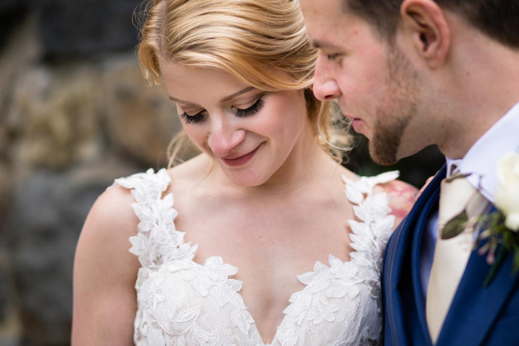 bride looks down to wedding ring whilst groom looks at bride