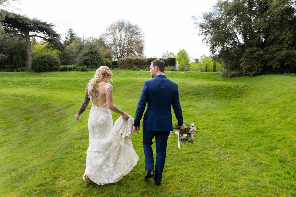 Tattooed bride Maira and groom Mark walk in the grounds at Chiswick House and Gardens