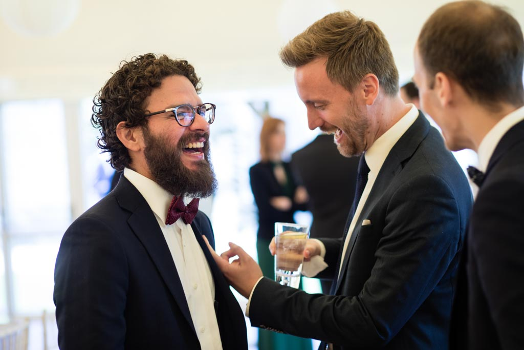 men laugh at burgundy bow tie of a wedding guest