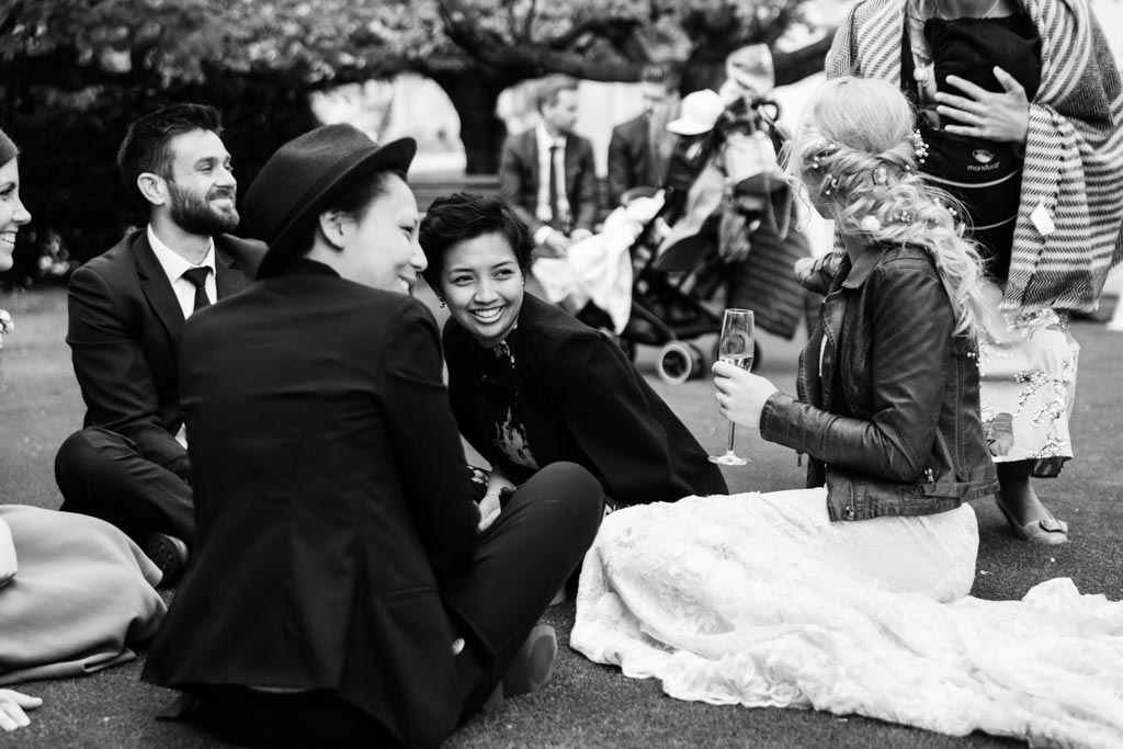 bride Maira wearing wedding dress and leather jacket chats with guests on the grass