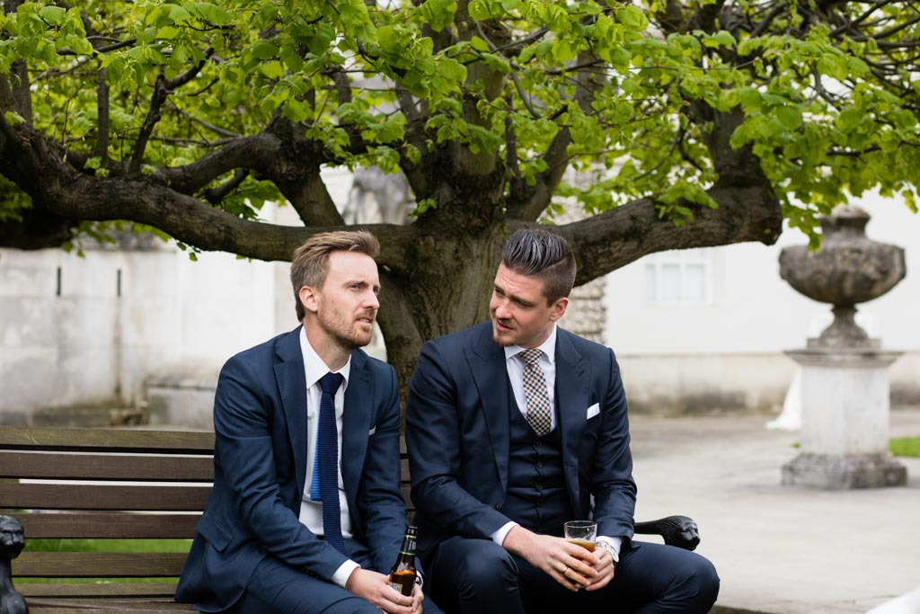 male wedding guests sit on a bench talking under a tree