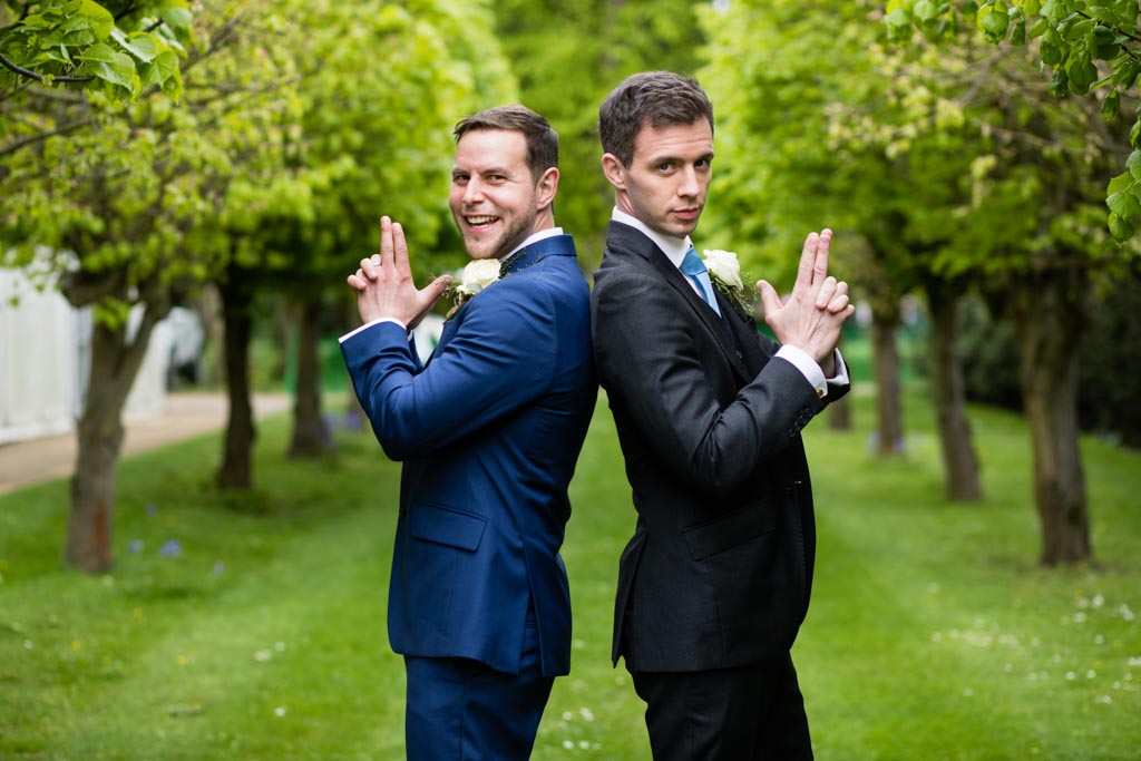 groom Mark and his bestman stand back to back in James bond pose