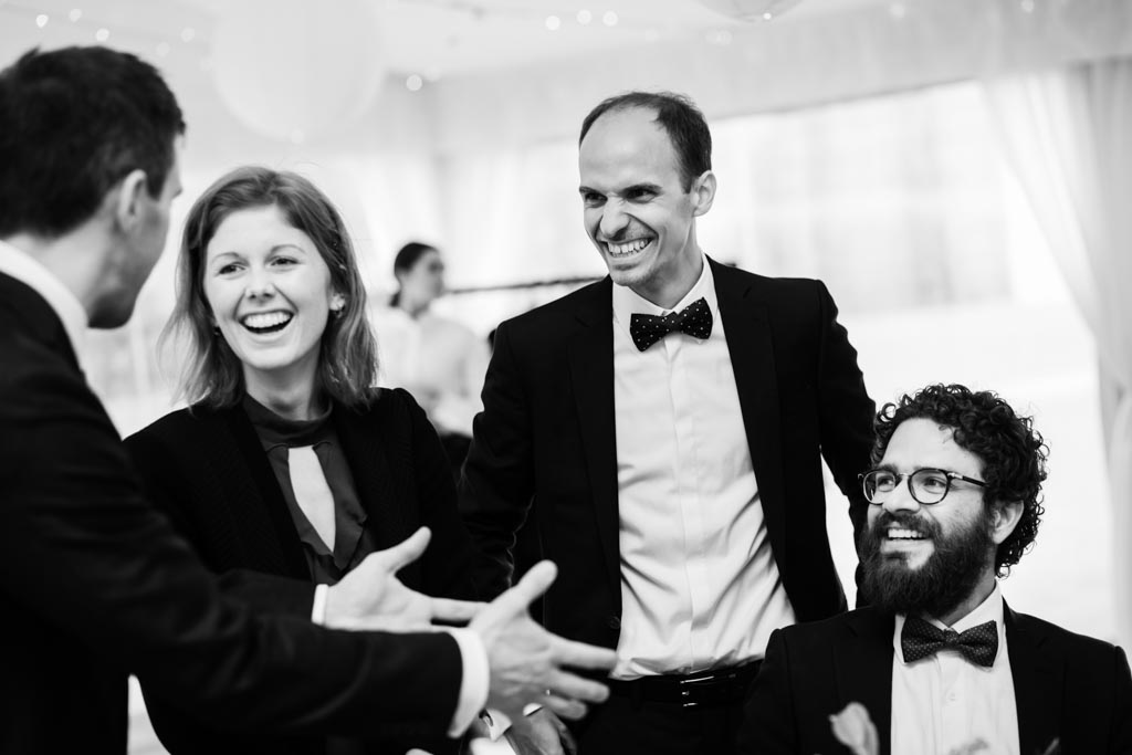 four guests laugh together at wedding