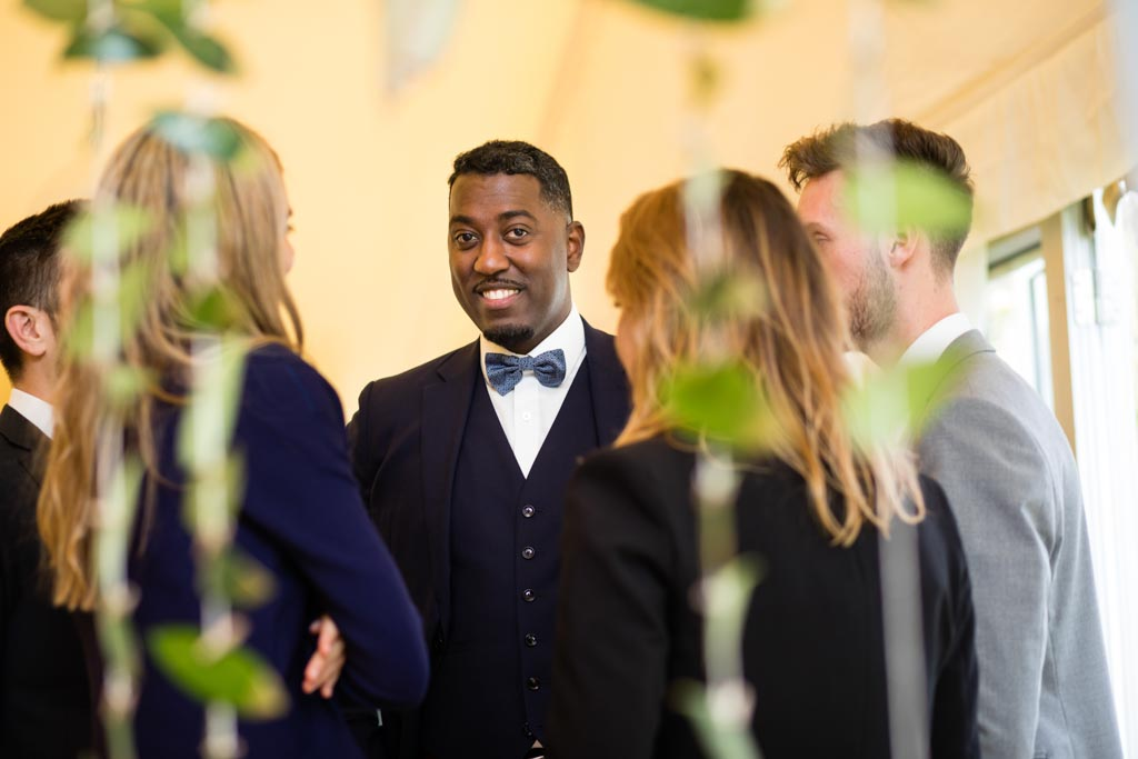 gentleman in blue bowtie smiles at the camera through wedding guests