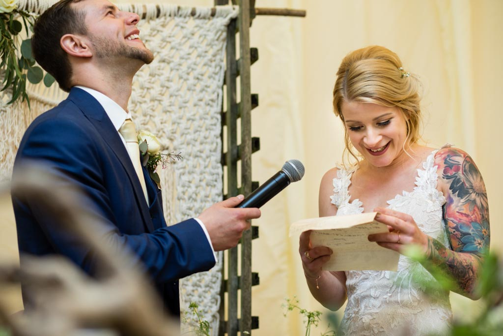 bride Maira reads her speech with laughing groom