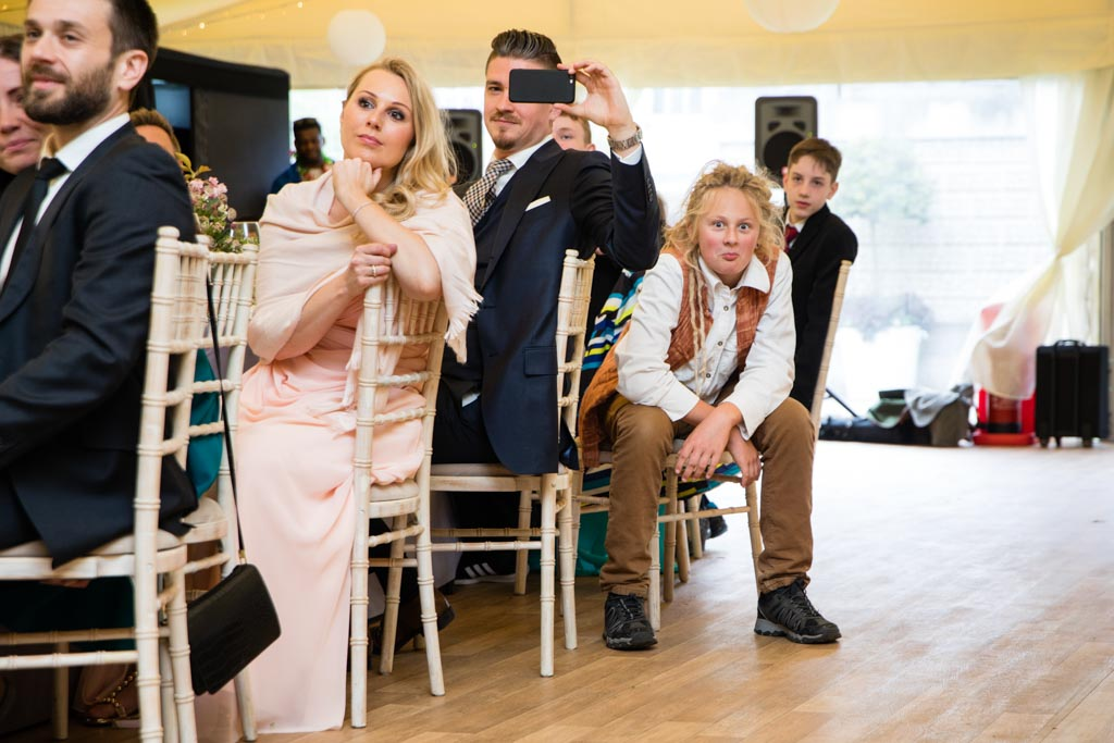 young wedding guest with dreadlocks makes a funny face