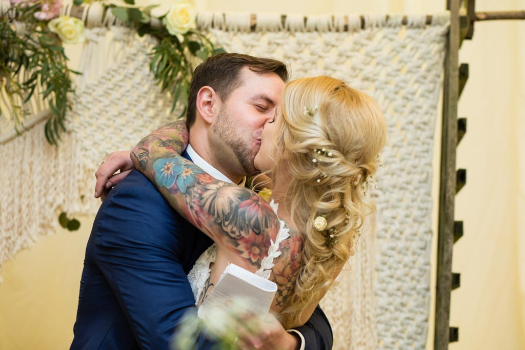 bride and groom kiss in front of a macrame backdrop