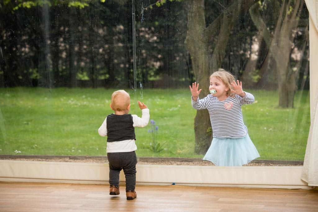 two children playing with the clear walls of a marquee