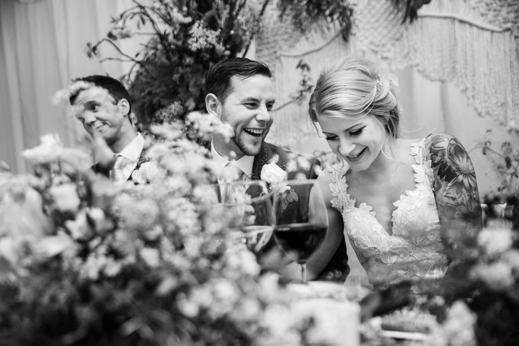 bride and groom laughing together among flowers