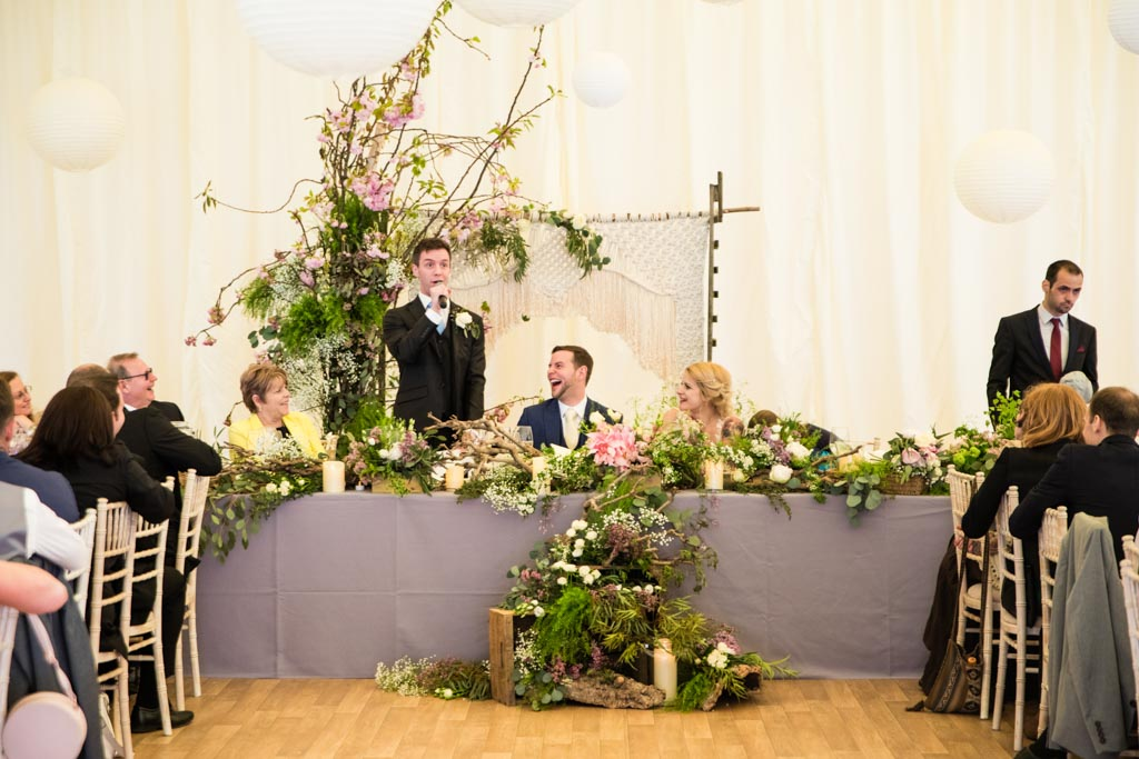 bestman gives his speech at the top table with macrame backdrop and flowers