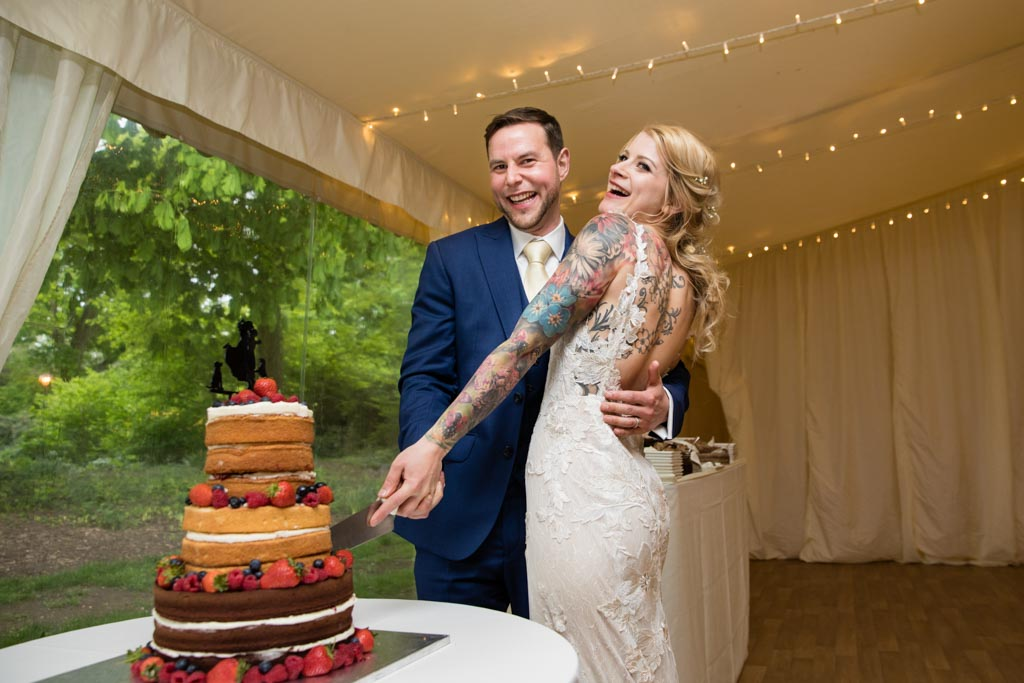 bride and groom laugh whilst cutting their wedding cake
