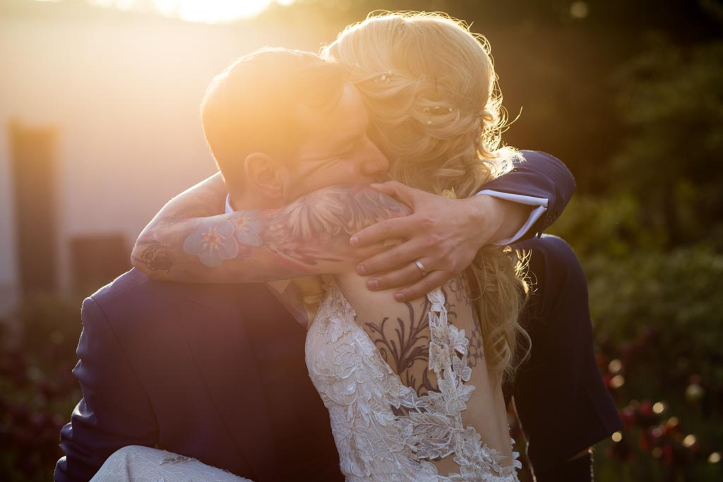 groom hugs his tattooed bride in the sunset