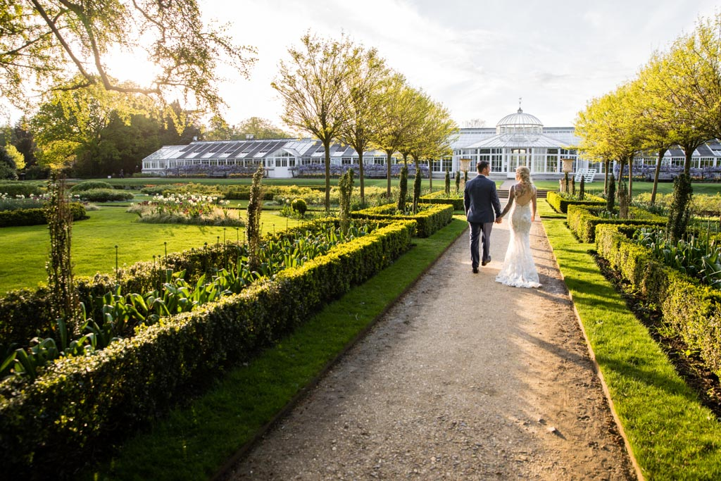 bride and groom walk through Chiswick House gardens to the conservatory