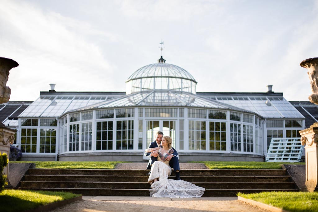 Maira and Mark sit on the steps in front of Chiswick House conservatory
