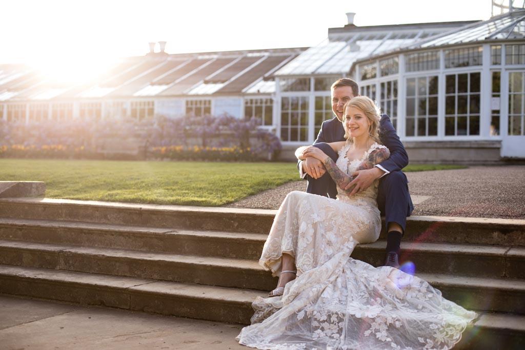 bride wearing David Fielden wedding dress sits on steps at sunset