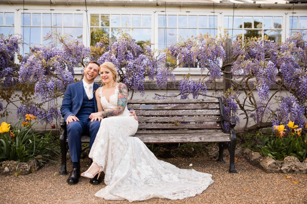 Maira and Mark sit on a bench with purple wisteria
