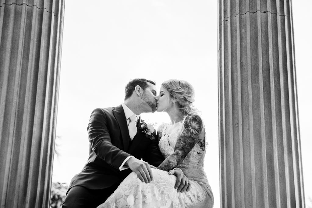 Maira and Mark kiss between columns