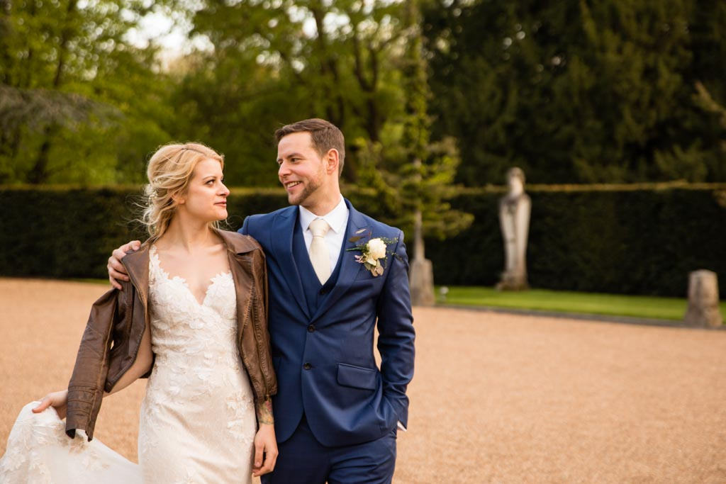 groom puts his arm around bride wearing leather jacket and David Fielden wedding dress