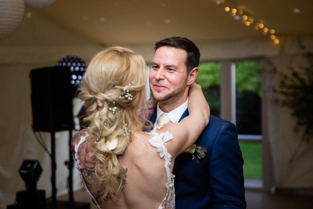 groom Mark smiles at his bride Maira