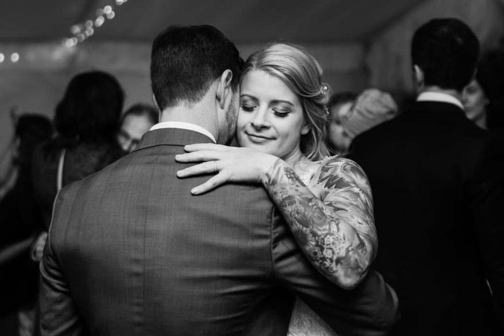 bride Maira hugs her husband with eyes closed