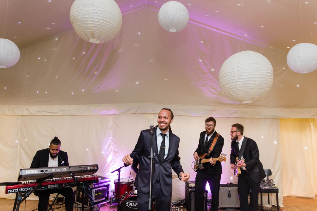 lead singer with band at a wedding with white lanterns