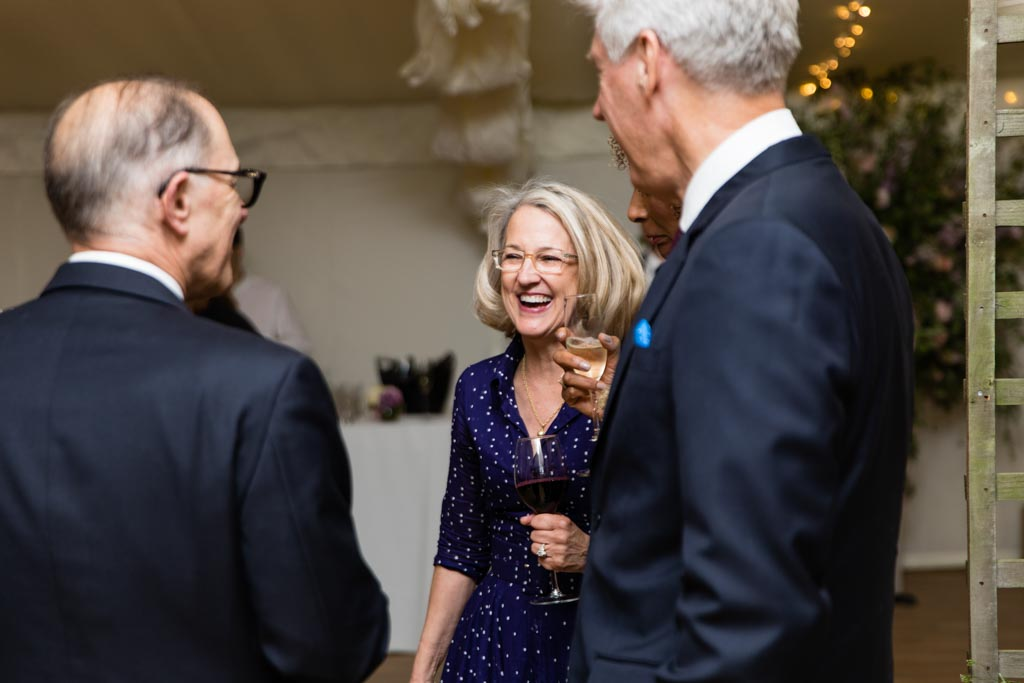 evening wedding guests laughing with drinks