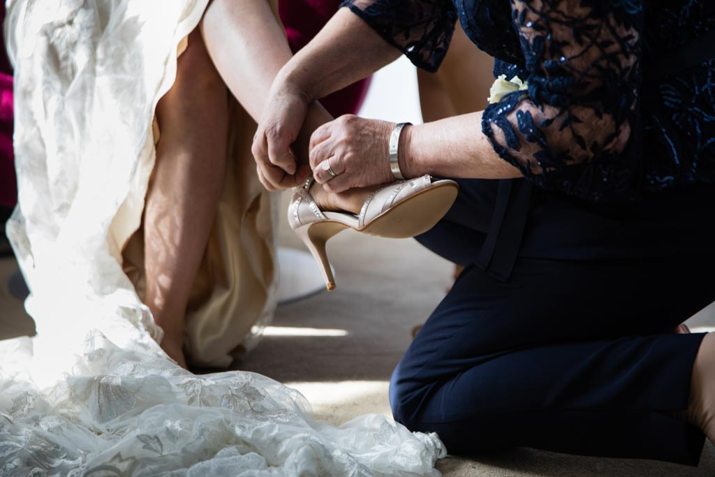 putting on bride's shoes