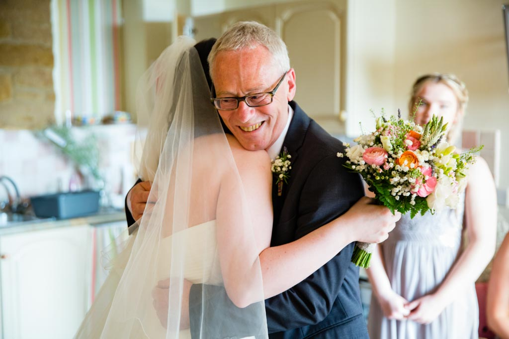 Father of the Bride hugs bride